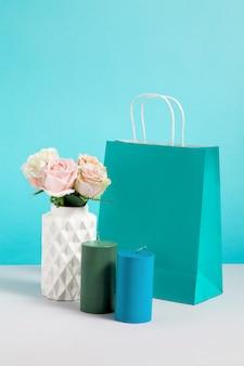 꽃병, 촛불 및 종이 가방에 꽃과 정물화 이미지. 공예 쇼핑백의 모형. 판매 또는 할인에 대한 개념. 브랜딩을 조롱하십시오. 파란색 배경에 장식 가게 복사 공간 이미지
