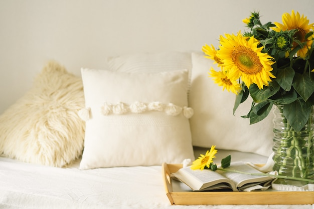 Натюрморт в домашнем интерьере гостиной. подсолнухи, кофе и открытая книга. читать, отдыхать