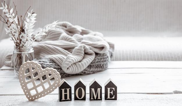 木の言葉の家、装飾の詳細、ニットの要素を備えたヒュッゲスタイルの静物。家の快適さとモダンなスタイルのコンセプト。