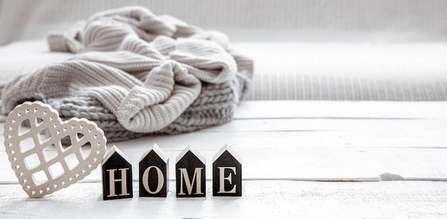 木製の単語の家とニットの要素を備えたヒュッゲスタイルの静物。家の快適さとモダンなスタイルのコンセプト。