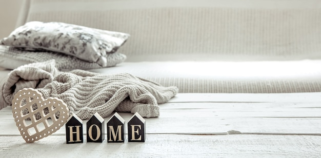木製の言葉の家、ハート、ニットの要素を備えたヒュッゲスタイルの静物。家の快適さとモダンなスタイルのコンセプト。