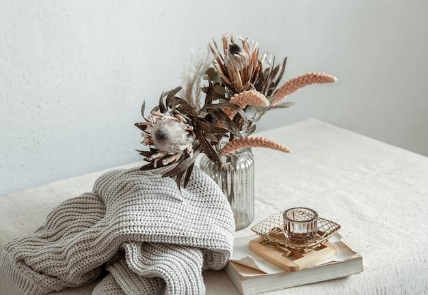 花の花束、ニットの要素、装飾的なディテールを備えたスカンジナビアスタイルの静物。