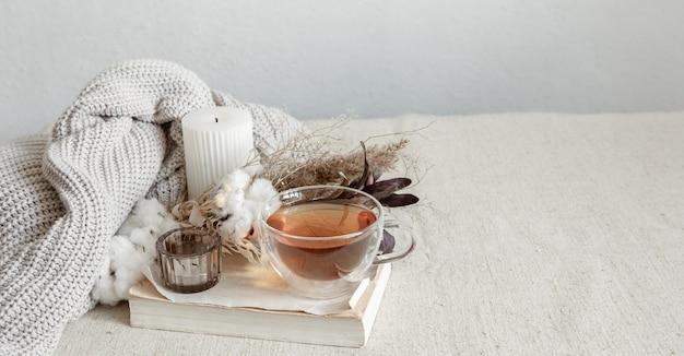 お茶、ニットの要素、本のコピースペースを備えたスカンジナビアスタイルの静物。