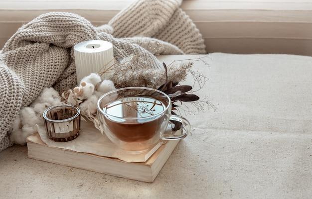 お茶、ニットの要素、本のコピースペースを備えたスカンジナビアスタイルの静物