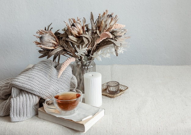 Натюрморт в скандинавском стиле с чашкой чая, вязанным элементом и книгой