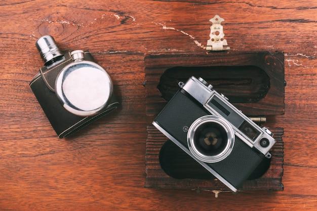 静物革シルバーヒップフラスコ古いカメラと木製の表面に木製の箱ヴィンテージコンセプト