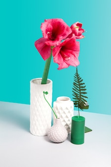 정물화 붉은 꽃, 흰색 세라믹 꽃병, 디자인을위한 공간을 가진 파란 배경에 회색 테이블에 장식을 모의. 꽃이 게 개념. 미니멀리즘 구성