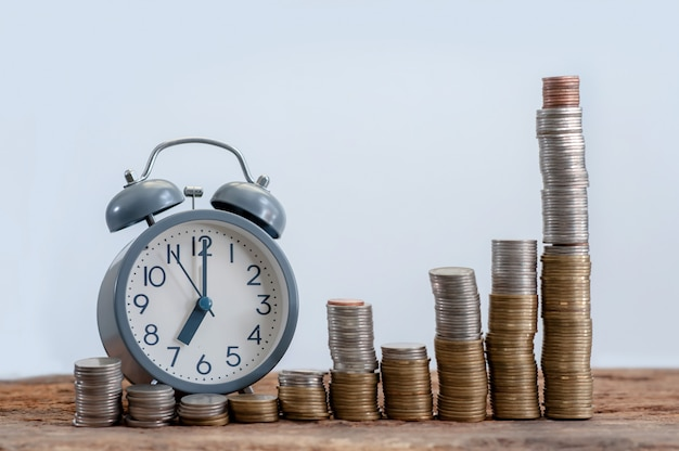 Still life of money stack step growing and alarm clock