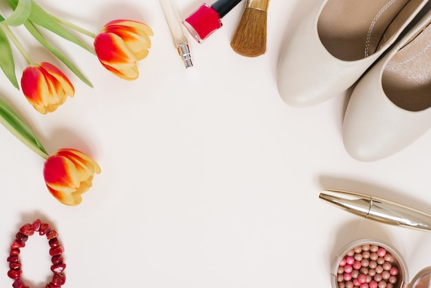 Натюрморт модницы. женский косметический фон. плоская планировка на день святого валентина. стильные аксессуары, букет тюльпанов и одежда блоггера. копирование пространства