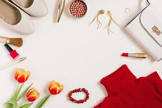 ファッショニスタの静物。女性の化粧品の背景。バレンタインデーのためのフラットレイ。スタイリッシュなアクセサリー、チューリップの花束、ブロガーの服。スペースをコピーする