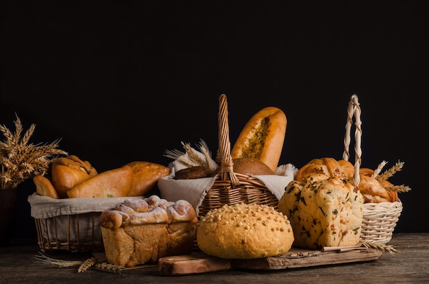 Натюрморт с разнообразным ассортиментом хлеба на черной стене