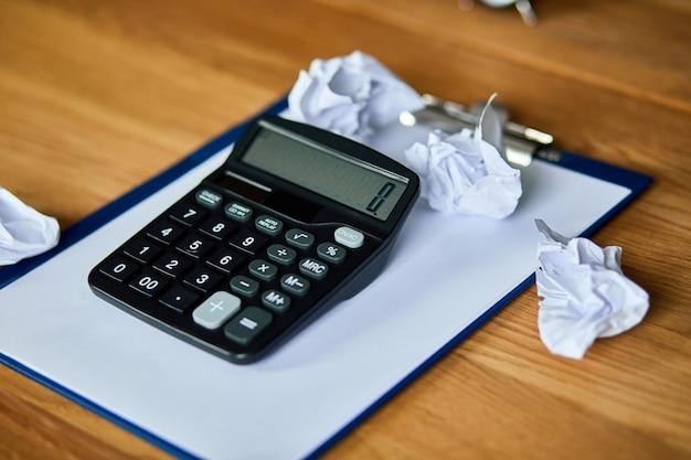 オフィスアクセサリー計算機、紙、ラップトップ、ノートブック、しわくちゃの紙のボールの木製テーブル、会計および銀行サービスを備えた会計士のワークスペースの静物。財政と支払い