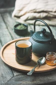 Натюрморт чашки черного чая с чайником на подносе над деревянным столом. чаепитие в уютной атмосфере
