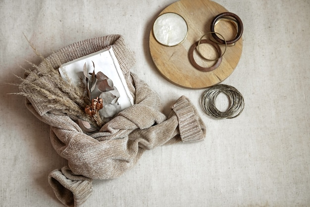 세부 사항의 정물. 따뜻한 스웨터와 여자 팔찌 평면도, 가을 개념에 말린 꽃의 꽃다발.