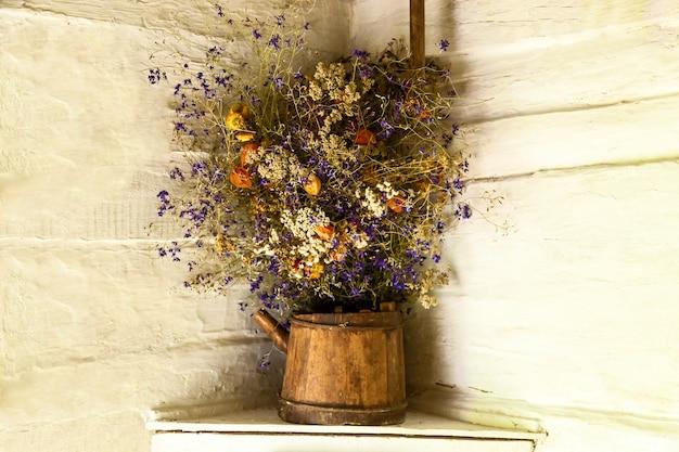 흰 벽 배경에 말린 꽃의 정물 오래된 돌의 틈새에 있는 야생 꽃 꽃다발