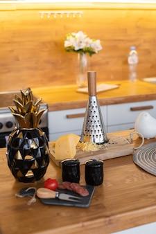 木製のまな板にフレッシュチーズとおろし金の静物。モダンなキッチンでの調理のプロセス。