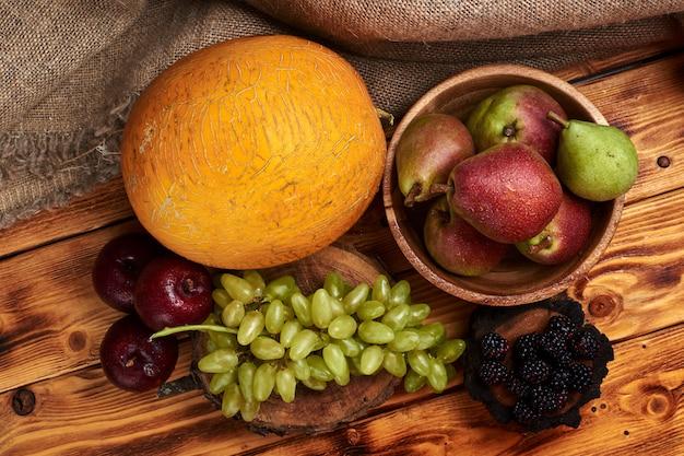 木製のテーブルにメロン、ブドウ、プラム、梨、ブラックベリーと新鮮な果物の静物
