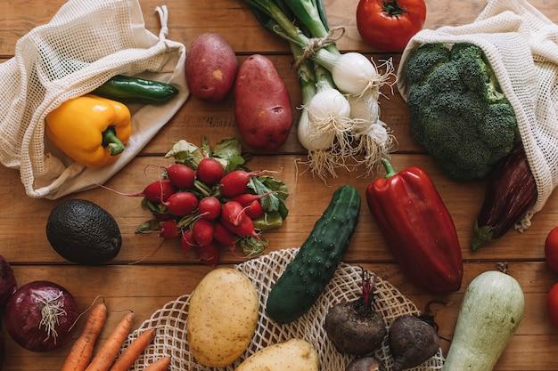 Натюрморт из свежих овощей в тканевых мешочках на натуральной деревянной основе