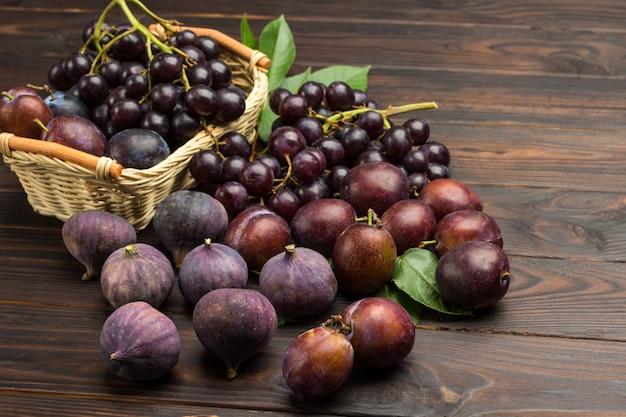 果物の静物。枝編み細工品バスケットのブドウの房。テーブルの上のイチジクとプラム。暗い木の空間。上面図