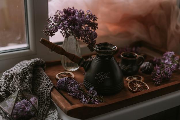 ライラック色の花、コーヒー、木製トレイのチョコレートの静物