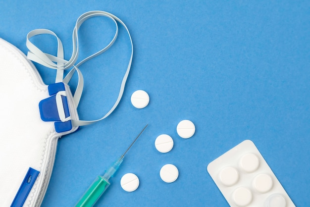 의료 개체의 정물화-파란색 표면에 독감 백신, 알약 및 바늘.