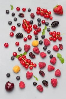 Натюрморт из разноцветных ягод на серой поверхности. красная смородина, малина красная и желтая, черника, зеленая мята. плоская планировка