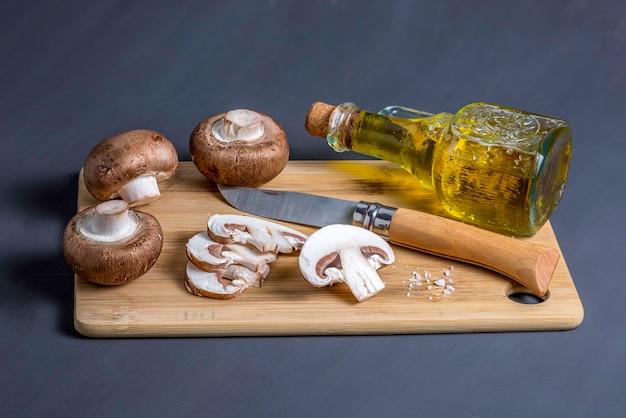 칼로 커팅 보드에 버섯 로얄 샴 피뇽의 정물과 올리브 오일 높은 각도보기와 병