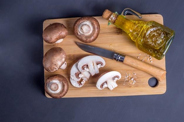 きのこの静物ナイフとオリーブオイルトップビューのボトルとまな板の上のロイヤルシャンピニオン