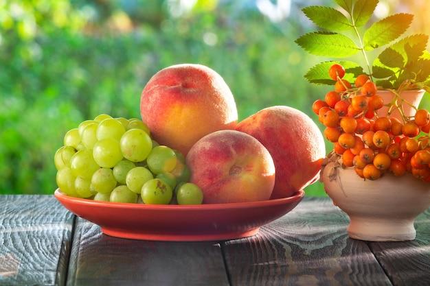 수확 후 나무 테이블에 복숭아 포도와 마가목 열매의 정물화
