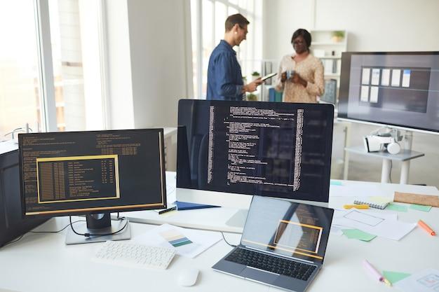 Натюрморт нескольких компьютерных экранов на столе в офисе ит-разработчиков с людьми на заднем плане, копией пространства