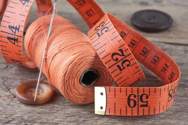 木製の背景に糸のスプールの静物