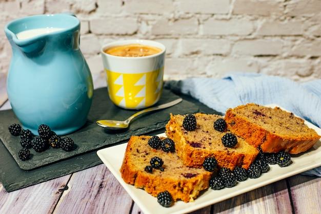 Натюрморт торта из диких фруктов с чашкой молока с какао и молочником.
