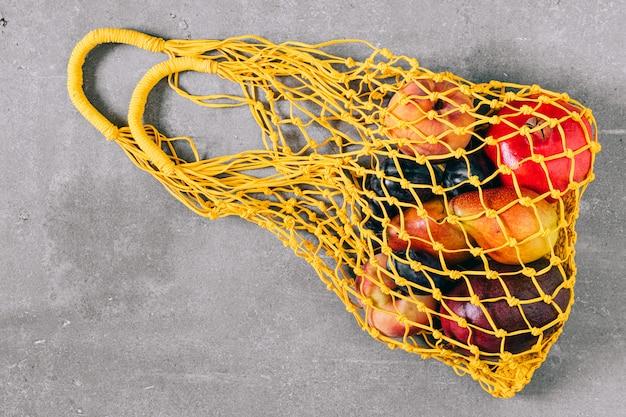 生の果物と黄色の生分解性ショッピングバッグの静物