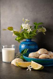 어두운 배경에 아직도 인생입니다. 레몬 쿠키와 테이블에 레몬 슬라이스, 꽃병에 우유와 꽃의 유리, 수직 위치