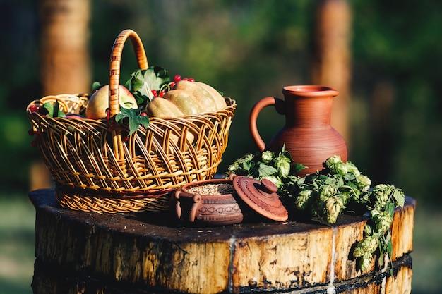 粘土の水差し、鍋の中の小麦、木製のデッキに飛び乗る、カボチャの入ったバスケット、リンゴ、ベリーなど、自然の静物画。