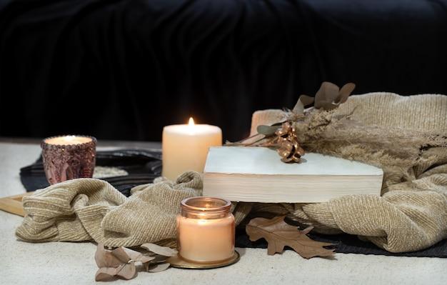 テーブルの上の静物本、ろうそく、暗いソファのスペースのお茶。秋の居心地のよさのコンセプト。