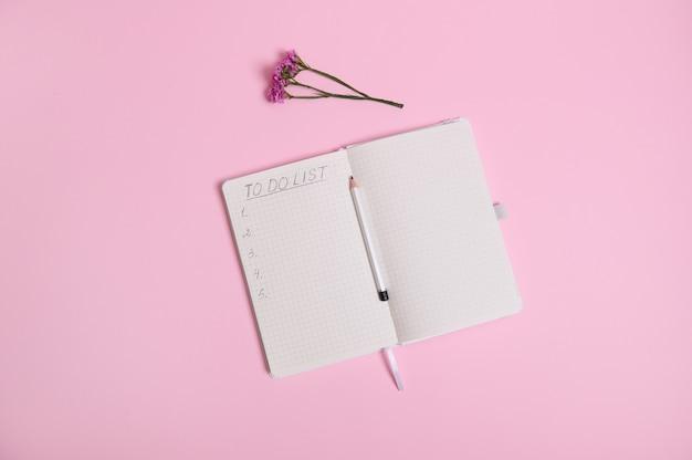 정물. 열린 의제, 일기, 복사 공간에 따라 흰색 종이에 할 목록이 있는 노트북, 의제 중간에 연필, 복사 공간이 있는 분홍색 배경에 초원 꽃