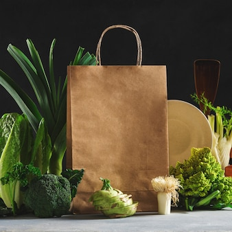 Still life paper bag with different health food on dark background