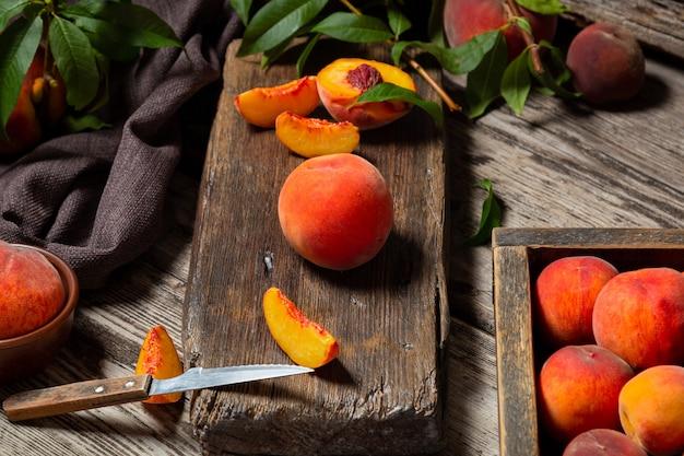 暗いキーのナイフでまな板の上の静物桃。ダークウッドの素朴なテーブルにジューシーな熟した桃。果物全体を半分にしたおいしい農場の桃、骨のある桃。