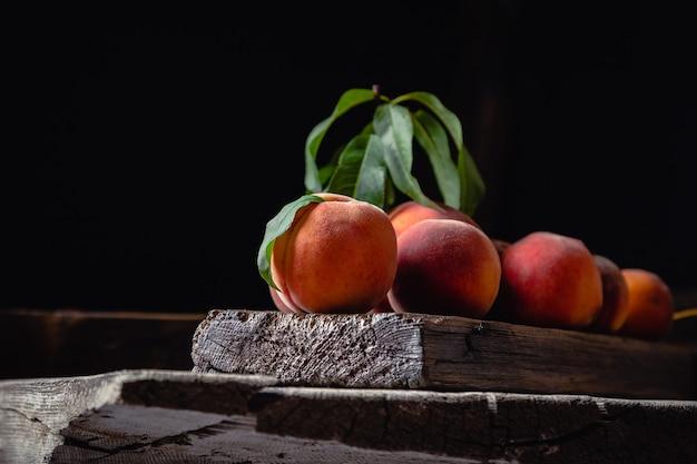 Персики натюрморта на ноже разделочной доски деревянного стола темное настроение. сочные спелые персики на темном деревянном деревенском столе. вкусные фермерские персики с листьями, целые плоды пополам, персик с косточкой.