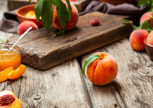 Still life peaches on wooden table with cutting board knife in dark key juicy ripe peaches