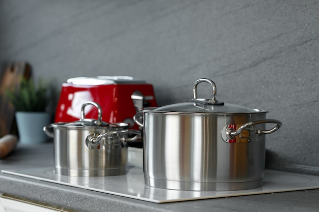 Still life photo of metal casseroles on induction stove in kitchen counter