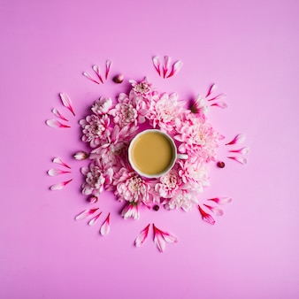 Still life photo top view of coffee with milk in a cup with chrysanthemum flowers around it