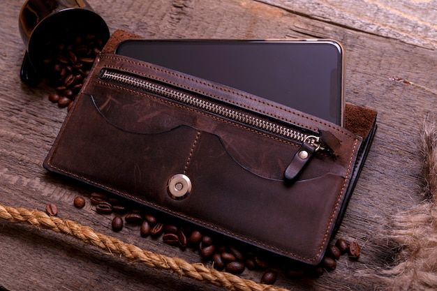 Still life photography of brown leather wallet, coffee beans, mobil phone and rope