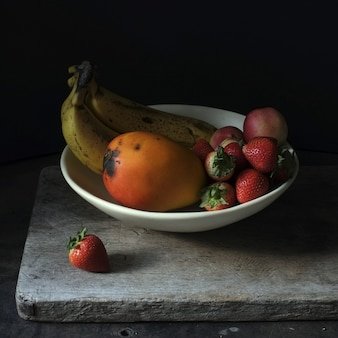 Фотография натюрморта свежих фруктов в белой тарелке на черном фоне