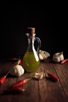 Натюрморт фотография бутылки оливкового масла перца чили и чеснока на деревянном столе