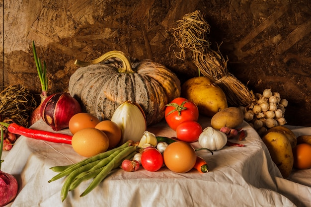호박, 향미료, 나물, 야채 및 과일을 가진 정물화 사진.