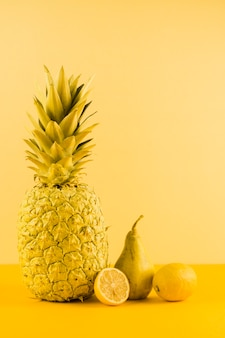 Still life of pineapple; lemon and pears against yellow backdrop