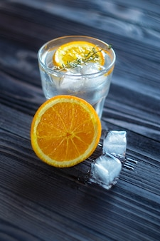 Still life of refreshing beverage with ice cubes and slice of orange