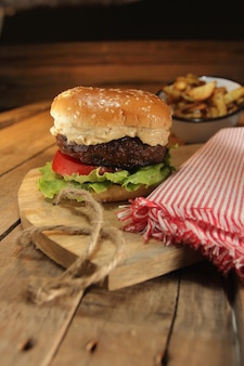 Still life of rustic burguer, french potatoes and props
